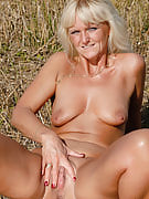 Golden-haired 43 yr old Jenny F undresses and spreads wide within the field