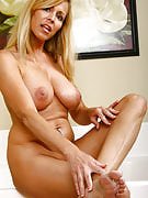 47 yr old busty golden-haired spreads her thighs and plays along with her feet