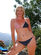 Sexy blonde MILF Tina poses naked outdoors by her swimming pool