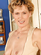 Older MILF flashes her adult pussy after finishing her coffee